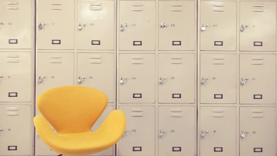 Yellow chair against lockers