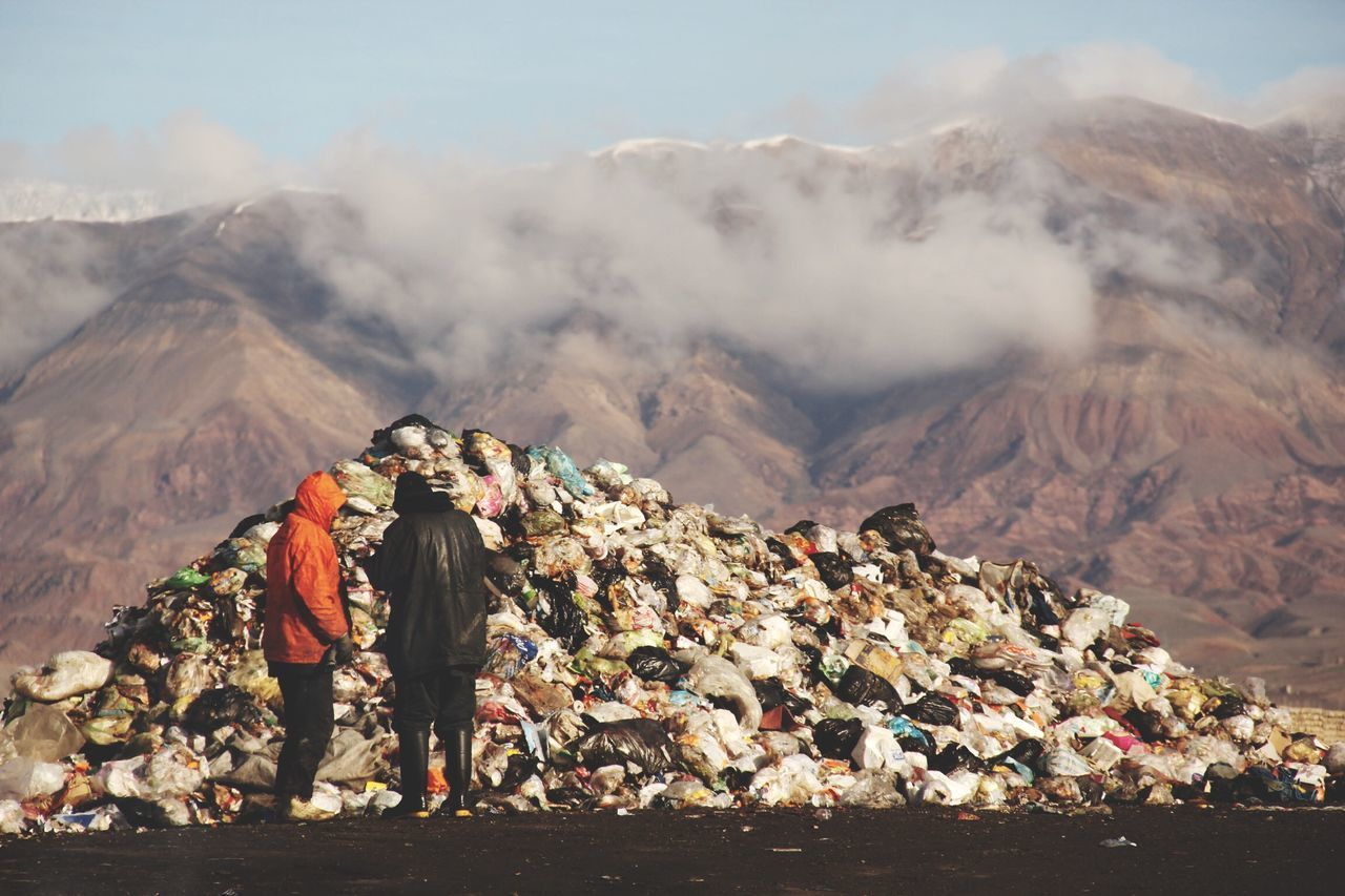 People standing in front of garbage against rocky mountains