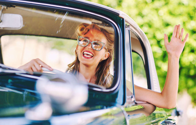 Smiling Woman Driving Vintage Car