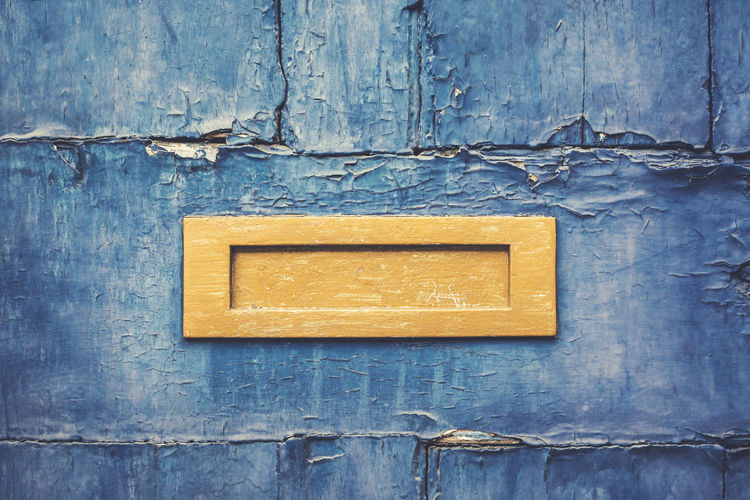An old painted wooden door with a bright yellow letterbox in it. Antique Classic Painted Rustic Weathered Background Blue Close-up Correspondence Door Entrance Letter Letterbox Mail Slot Mailbox No People Old Peeling Off Postal Seamless Straight On Texture Vintage Wooden Yellow