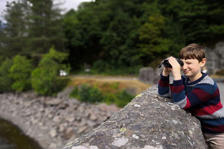 Boy looking through binoculars by retaining wall