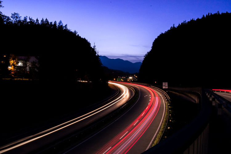 Blue Blurred Motion City Life Diminishing Perspective Illuminated Light Trail Lit Long Exposure Motion Mountain Night Outdoors Outline Red Road Rush Hour Sky Speed Tail Light The Way Forward Transportation Vanishing Point