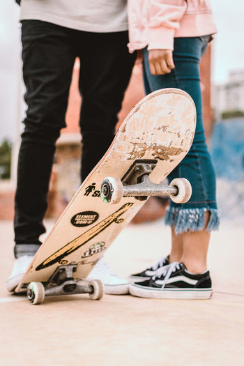 Couple in skate park with skateboard Chuck Taylor Converse Couple Skateboarding All Star Close-up Converse All Star Jeans Outdoors People Real People Skate Skate Park Skateboard Skateboard Park Sport Sports Ramp Standing Vans Vans Off The Wall Vansoffthewall
