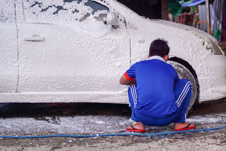 Washing the vehicle Wash The Tires Car Washing Working One People Real Life Snow Wash Soap Bubbles Wash Car Wash Car Foam Washing Soap White Car
