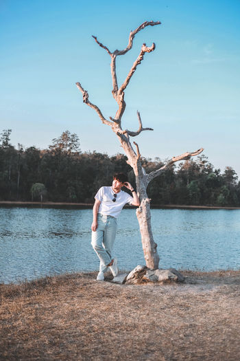 Man standing on tree by lake against sky
