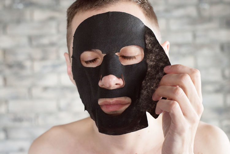 Close-up of man removing facial mask at home