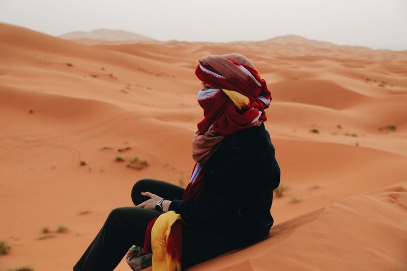 a woman in the ocean of sands. Morocco Land One Person Real People Sand Desert Lifestyles Landscape Clothing Environment Sitting Leisure Activity Women Nature Sand Dune Adult Scenics - Nature Day Beauty In Nature Climate Arid Climate My Best Photo The Great Outdoors - 2019 EyeEm Awards
