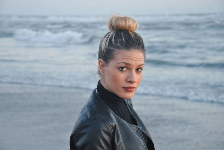 Side view portrait of confident woman with hair bun standing at beach