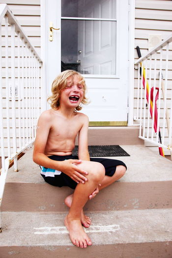 Boy Crying In Pain While Sitting On Steps Outside House