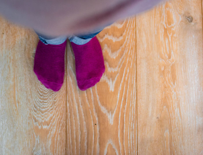 Perspective view of a kid's feet with purple socks and blue jeans Children Foot Happy Infancy Jeans Steps Childhood Close-up Concpetual Day Floor Human Body Part Human Hand Human Leg Indoors  Lifestyles Low Section One Person Pair People Real People Small Sock Two People Wooden