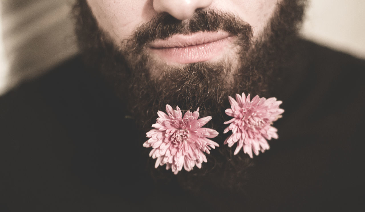 Midsection of man beard with pink flowers