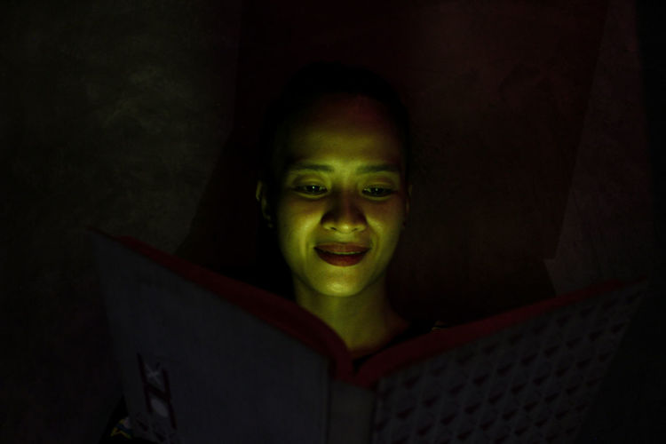 Portrait of smiling young woman in darkroom