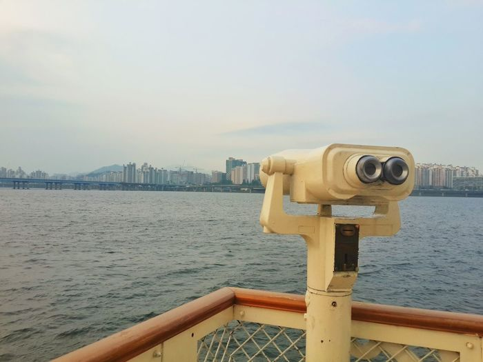 Close-up of coin-operated binoculars at sea against sky