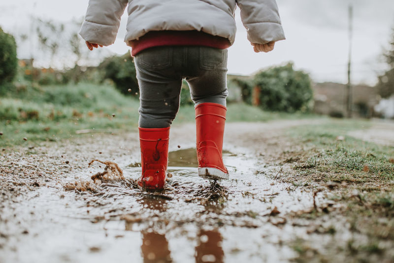 Low section of baby girl walking on puddle during rainy season