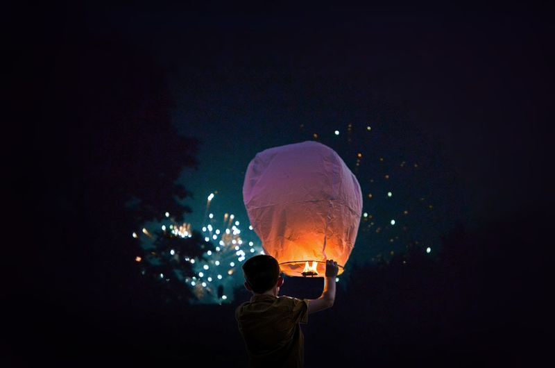 Rear view of boy holding illuminated lantern at night