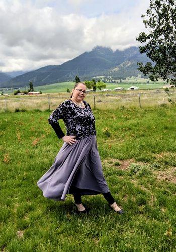Portrait Of Woman Walking On Field Against Sky