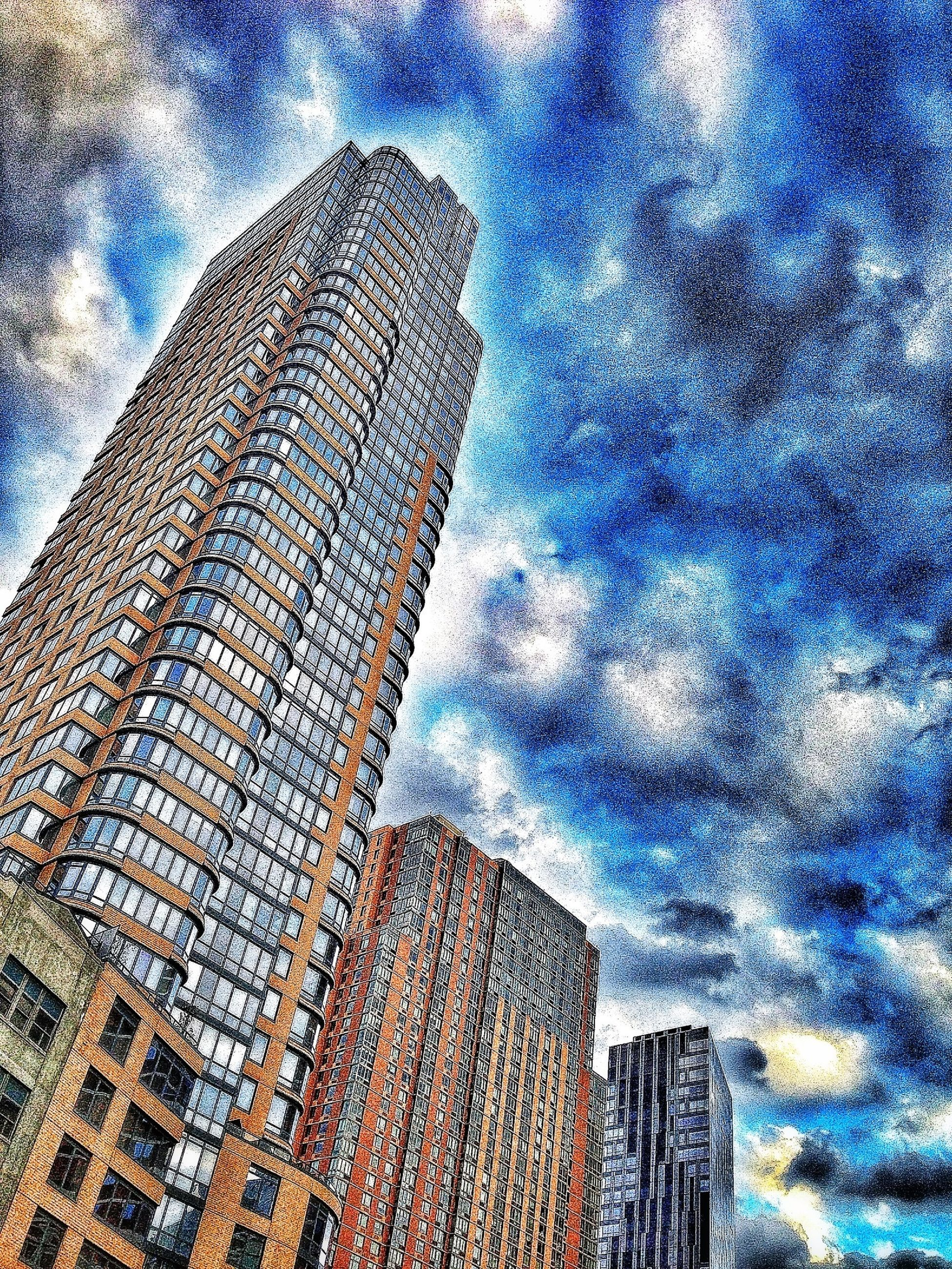 low angle view, building exterior, architecture, sky, built structure, tall - high, cloud - sky, tower, skyscraper, modern, city, cloudy, office building, tall, blue, cloud, famous place, outdoors, no people, day