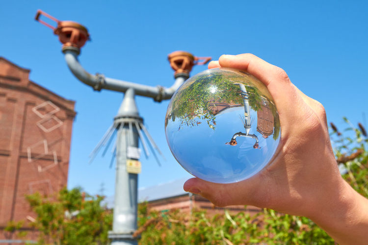 Protego cap Protego Protego Cap Sphere Architecture Blue Body Part Building Exterior Built Structure Clear Sky Day Finger Focus On Foreground Hand Holding Human Body Part Human Hand Low Angle View Nature One Person Outdoors Plant Real People Sky Sphere Tree