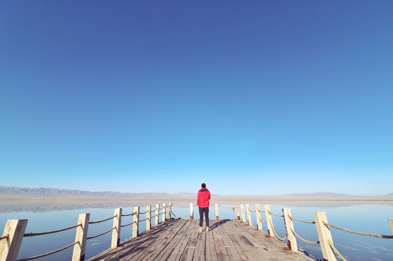 Rear view of man standing on pier over lake against clear blue sky