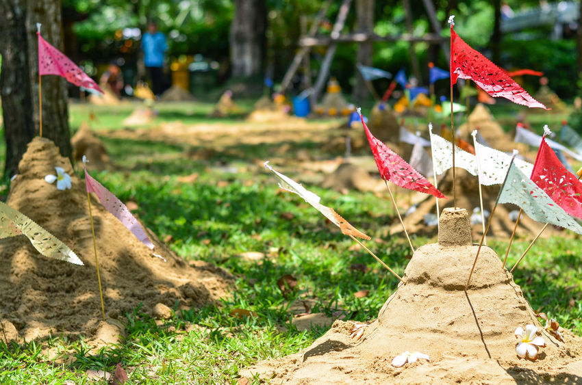 Nakhon Pathom, Thailand-April 14, 2018: Tradition of carrying sand into the temple and making sand pagoda is one of Thai traditional in the Songkran Festival of Thai Traditional New Year's Day during April of 13th-15th every year. April Of 13th-15th Every Year EyeEm Best Shots EyeEmNewHere Songkran Festival Thai Traditional New Year's Day Tradition Of Carrying Sand Into The Temple Belief Close-up Day Focus On Foreground Grass Nature No People Outdoors Pagada Park Plant Religion Representation Sand Pagoda Sky Sunlight Tree