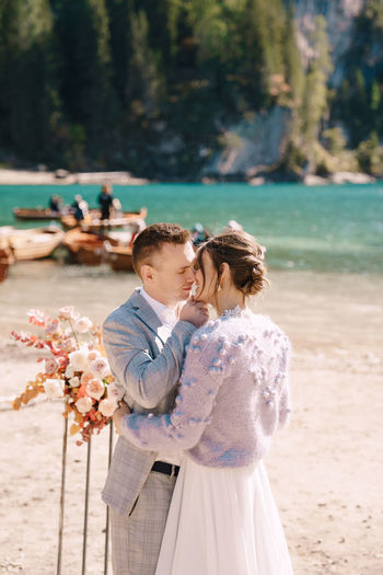 Couple embracing while standing at riverbank