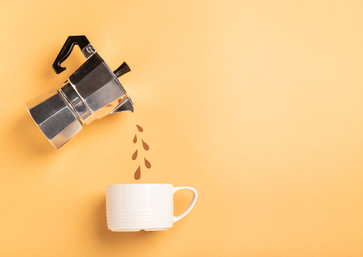 Close-up of coffee cup on table against orange background