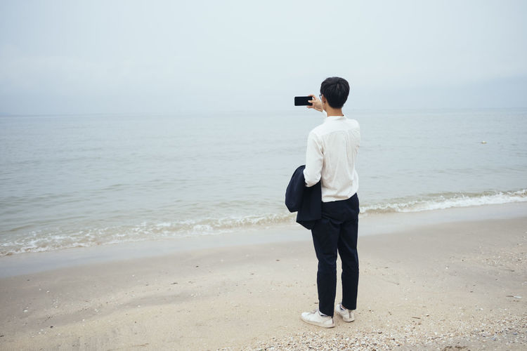 Full length rear view of man photographing sea