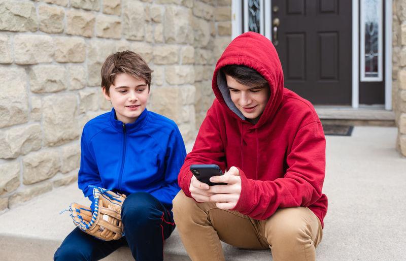 Full length of teenage boy sitting on mobile phone