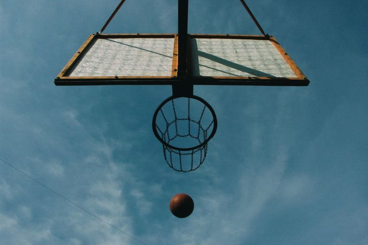 Low Angle View Of Basketball By Hoop Against Sky