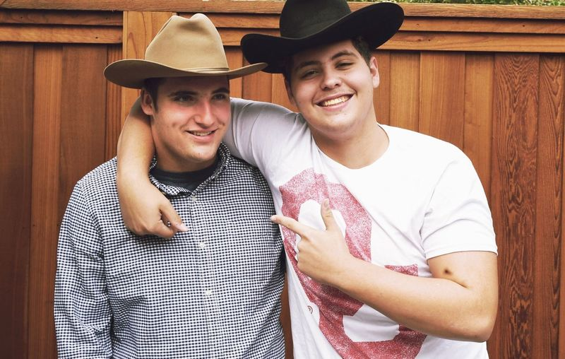 Vintage Hats Brother Hug Joviality Brothers Cowboy Hats  Teenagers  American South Enjoyment Cowboy Hat Smiling Happiness Emotion Hat Young Men Togetherness Two People Young Adult Portrait Clothing Cheerful Males  Friendship Waist Up Positive Emotion Casual Clothing
