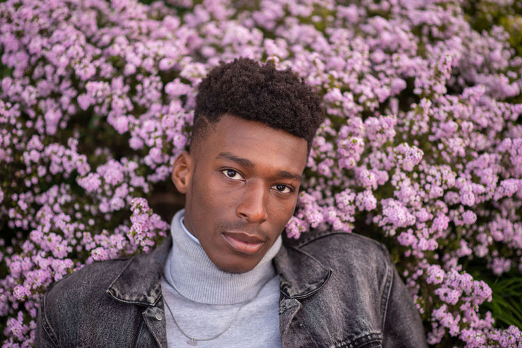 Portrait of young man against pink flowers