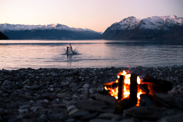 Fire made and lit to keep warm after jumping into Lake Hawea in the south island or New Zealand. Beach Campfire Camping Flame Lake Landscape Mountain Nature New Zealand Outdoors Snow Sunset Swim
