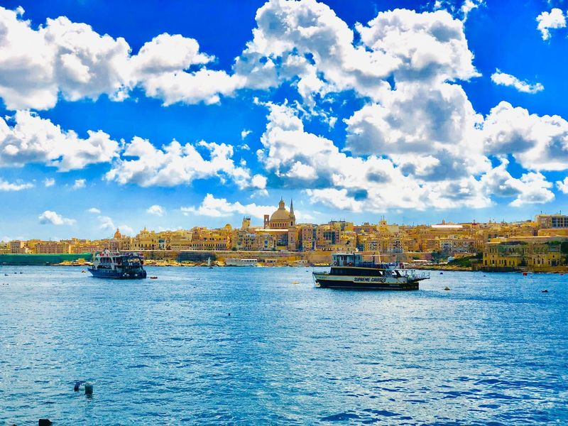 Cityview on Valletta, Capital City of Malta, Europe, view from Sliema, Basilica of Our Lady of Mount Carmel and St. Paul's Anglican Cathedral Mediterranean  Island Skyline Cityview Cityscape Church Carmelite Water Site Landmark Historic European  Picturesque Destinations Destination Travel Town Old Malta Maltese Ferry Clouds Cloud Mode Of Transportation Sky No People Blue Architecture Day Ship