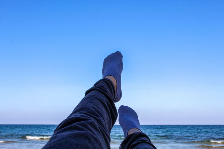 Low section of person wearing sea against clear blue sky