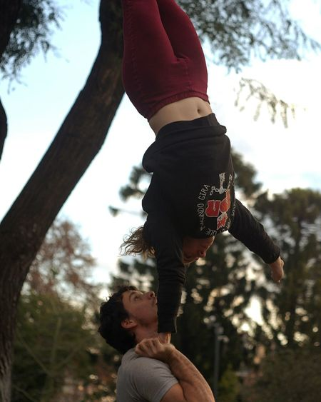 Young Woman Doing Acrobats With Man At Park
