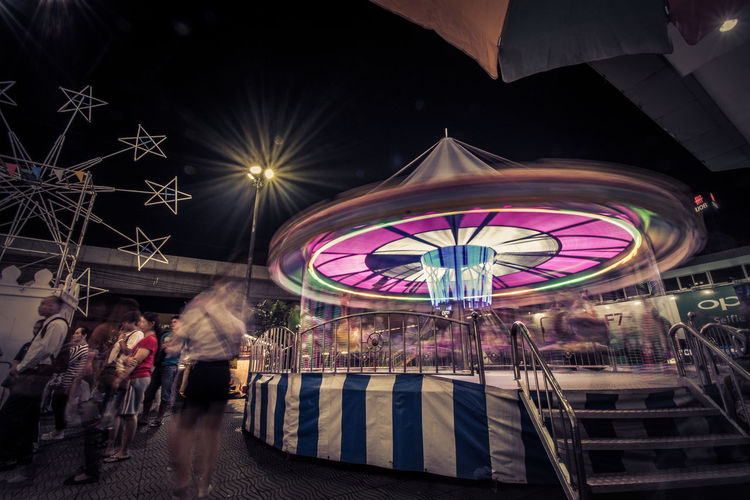 Adult Amusement Park Amusement Park Ride Architecture Blurred Motion Building Exterior Built Structure City Illuminated Incidental People Leisure Activity Lifestyles Men Motion Multi Colored Night Nightlife Outdoors Real People Street Transparent Women EyeEmNewHere