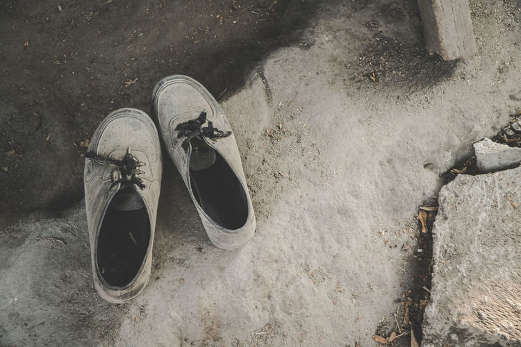 Shoe Pair High Angle View Still Life No People Absence Fashion Land Day Outdoors Abandoned Personal Accessory Compatibility Boot Close-up Two Objects Shoelace Nature Dirt Dirty Rubber Shoes Rubber Shoes And Pants