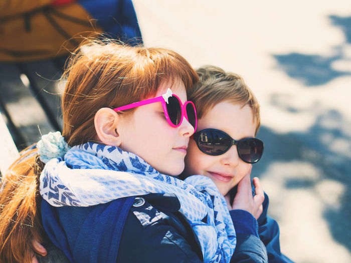 Siblings wearing sunglasses while embracing outdoors