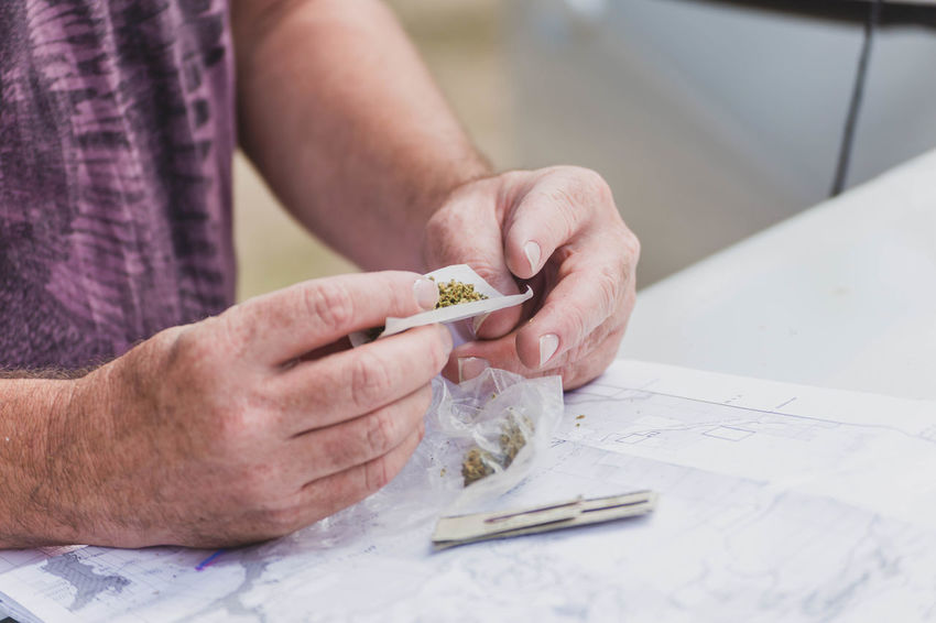 Man rolling a cannabis joint over a map. Calming Cannabis Industry Medicine Weed Life Activity Art And Craft Close-up Finger Focus On Foreground Hand Holding Human Body Part Legal Legalization Legalizeit Men One Person Paper Real People Skill  Tax Revenue Taxes Weed Working