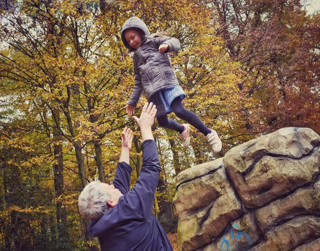 Full length of father and son against trees during autumn
