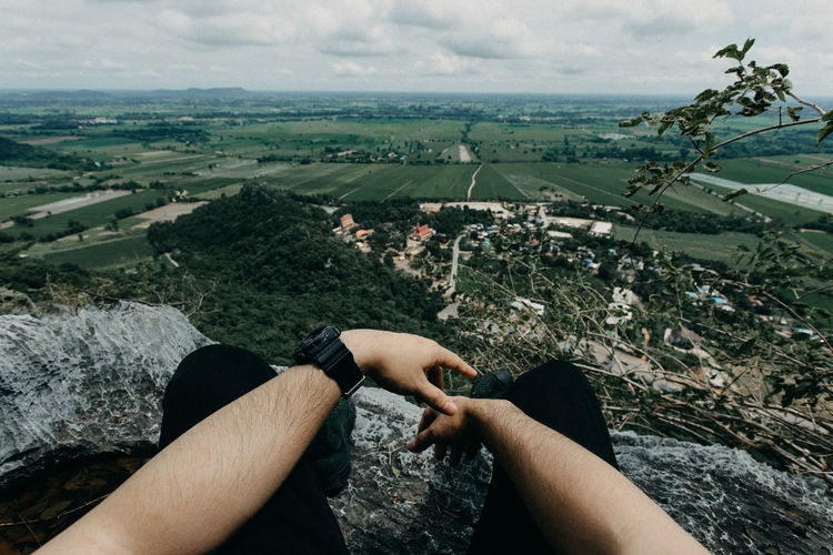 Low section of man sitting on rock against landscape
