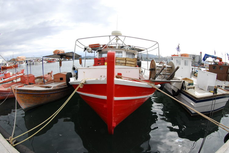 Fishing boat moored at harbor against sky