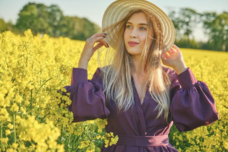 Portrait of beautiful young woman wearing hat on field