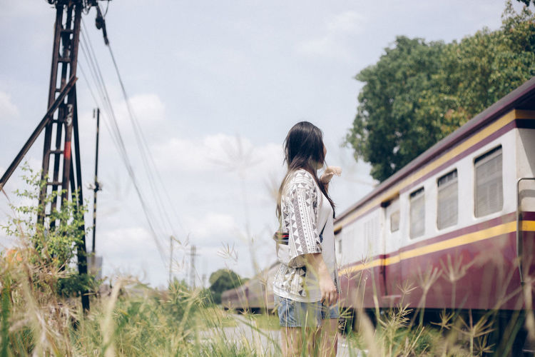 Side view of woman standing on land by train against sky