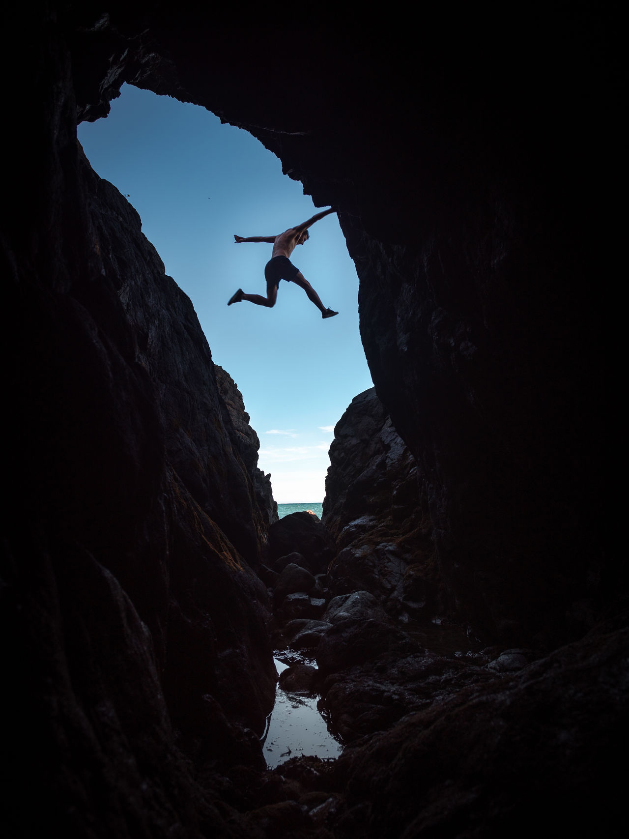 Low angle view of man jumping over rock formation against sky