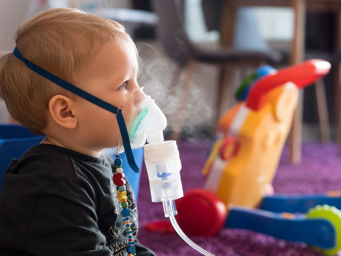 Blonde caucasian small boy with oxygen mask making inhalation at home Child Childhood Inhalation Kid Inhaler Medical Asthma Home Medicine Boy Health Allergy Asthmatic Care Respiratory Patient Treatment Young Sick Disease Illness Breathing Oxygen Mask Little Caucasian Face Therapy Airplane Flu Inhaling Medication Allergic Casual Clothing Side View
