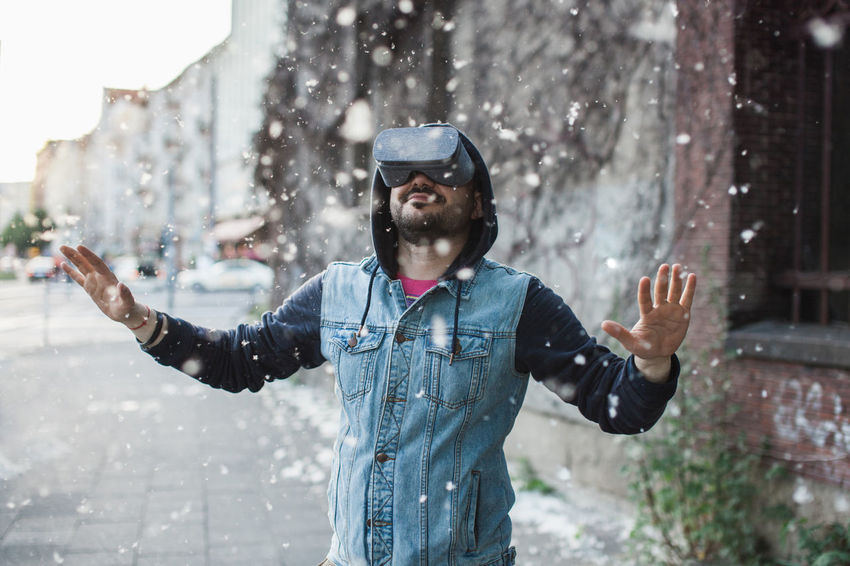 Man wearing VR goggles on a street during summer day while cottonwood fluff is flying around Arms Arms Outstretched Arms Raised Beard Cottonwood Flying Hands Headset Hipster Jeans Man Modern Out Outdoors People Technology Virtual Reality Virtual Reality Headset Virtual Reality World Vr Young Adult