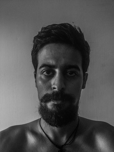 Portrait of young shirtless man in beard