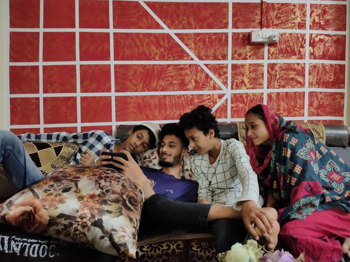 Group of people sitting on bed