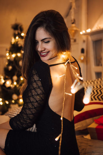 Young Adult Smiling Happiness Young Women One Person Beautiful Woman Christmas Women Clothing Beauty Lifestyles Emotion Illuminated Three Quarter Length Indoors  Leisure Activity Winter Decoration Waist Up Hair Hairstyle Warm Clothing